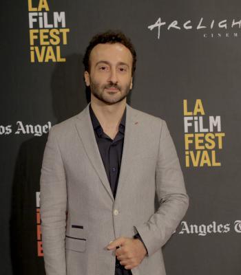 Man standing in front of black LA Film Festival backdrop