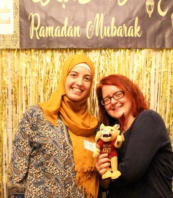 Two women friends posing in front of a Ramadan Mubarak sign with stuffed animal
