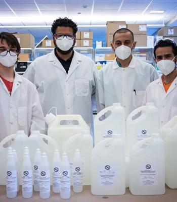 Four masked students in a lab