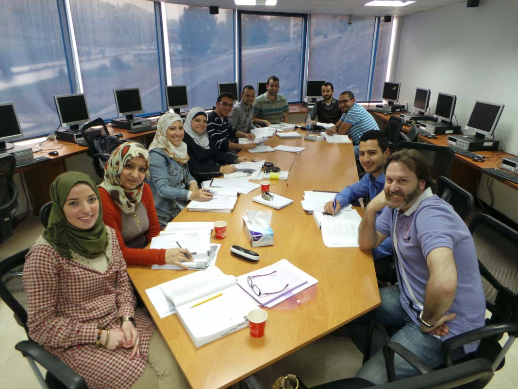 A group of graduate students sit around a table and smile at the camera, there are pens and papers in front of them