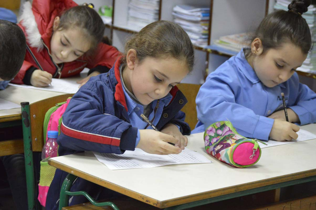 Young female students write at desks