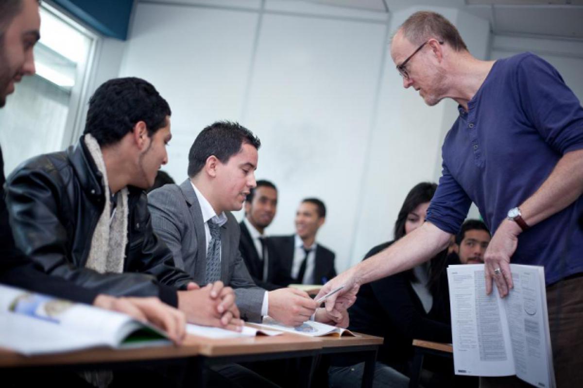 A teacher talks to students sitting at desks