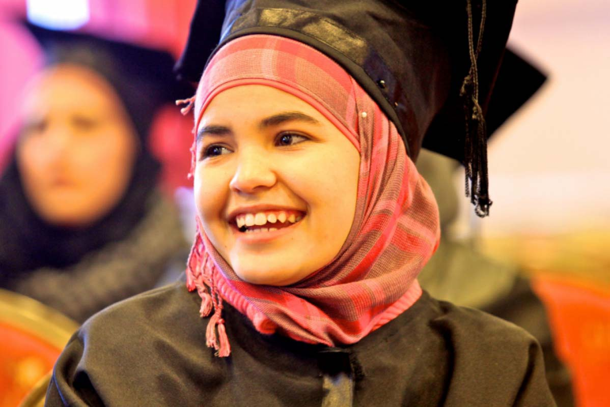 Female graduate smiles in cap and gown