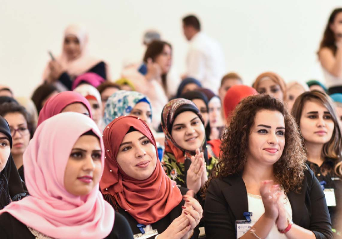 Young women graduates of AMIDEAST's Skills for Success program in Lebanon sit in a large room for the ceremony