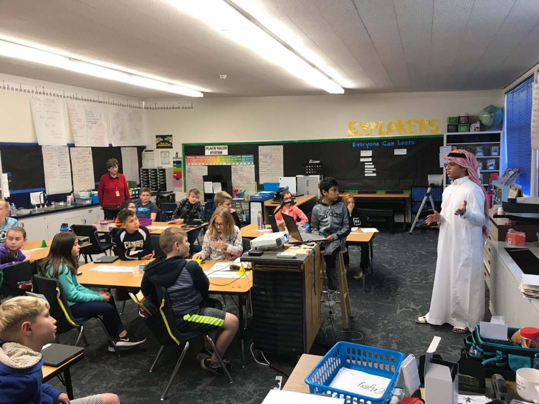 Picture of Saudi exchange student teaching American grade school youth about Saudi Arabia