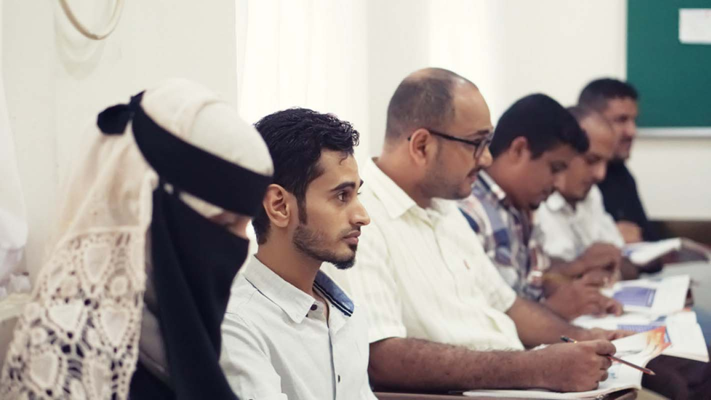 Yemeni high school students listening to an educational adviser in a classroom