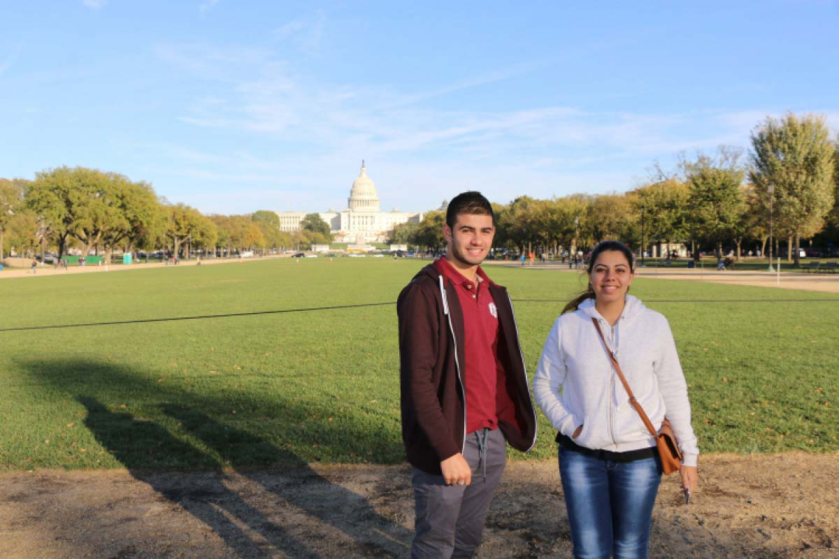 Two students stand in front of the U.S. Capitol building