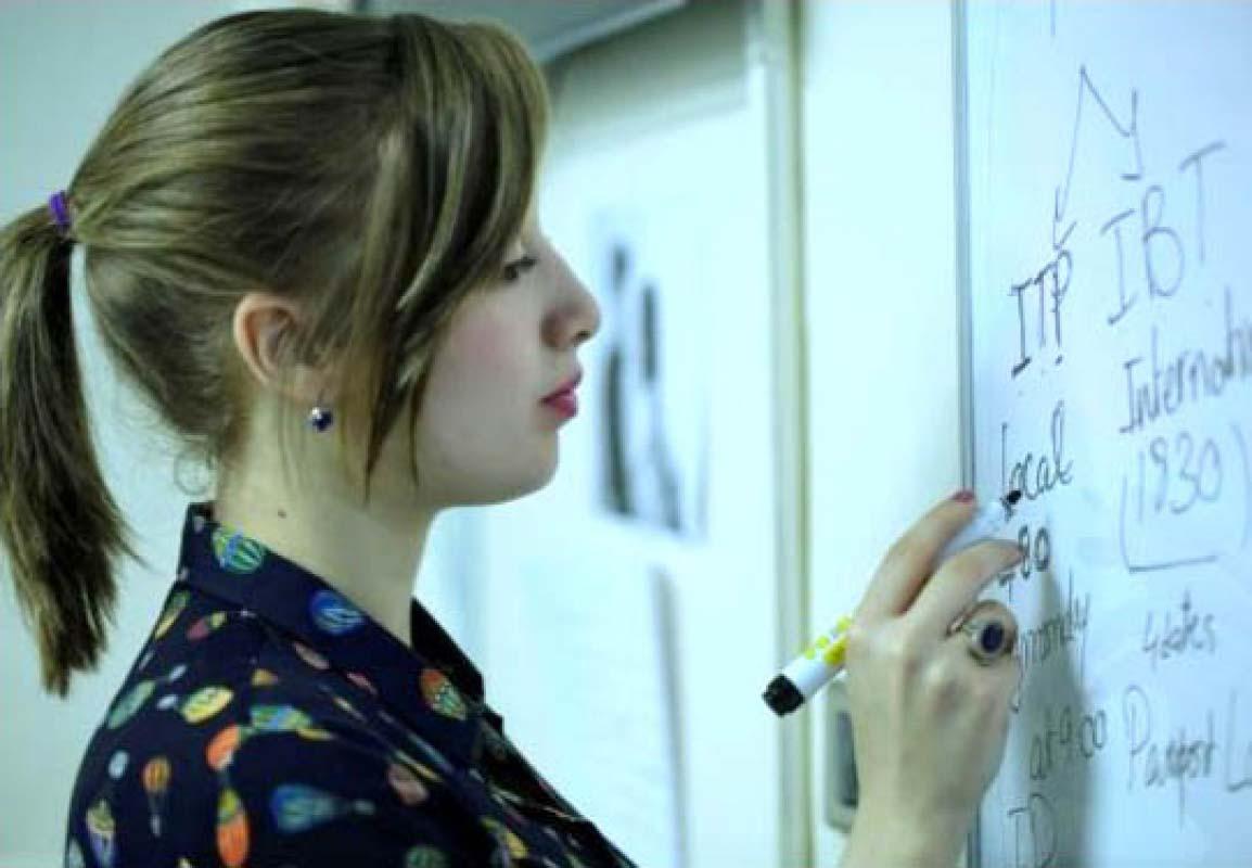Female student writes on a whiteboard