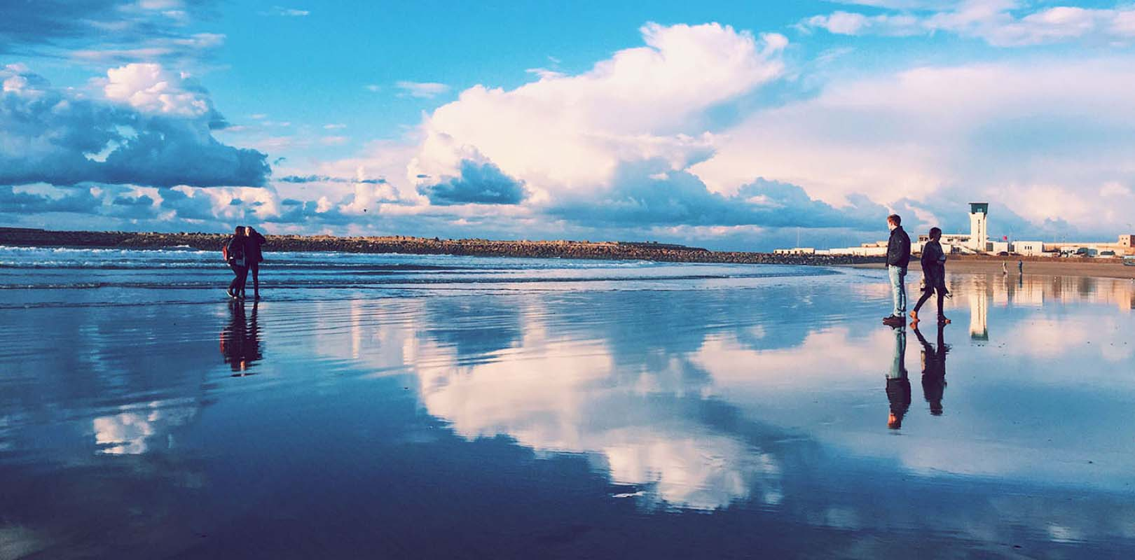 Clouds reflect on the water on the beach in Rabat, Morocco