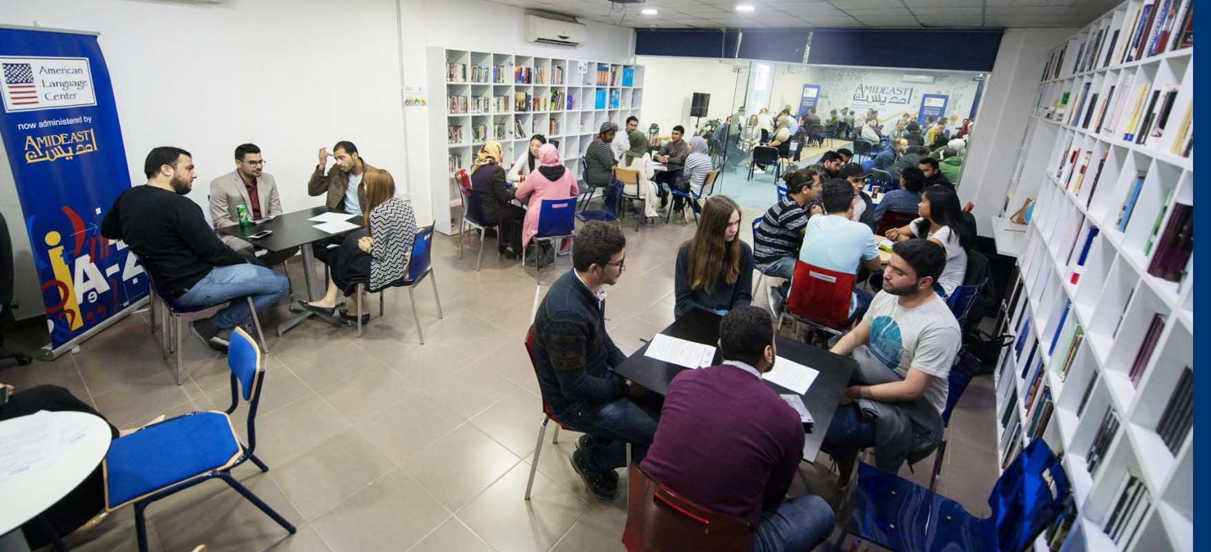 Students sit at tables while practicing their English with each other