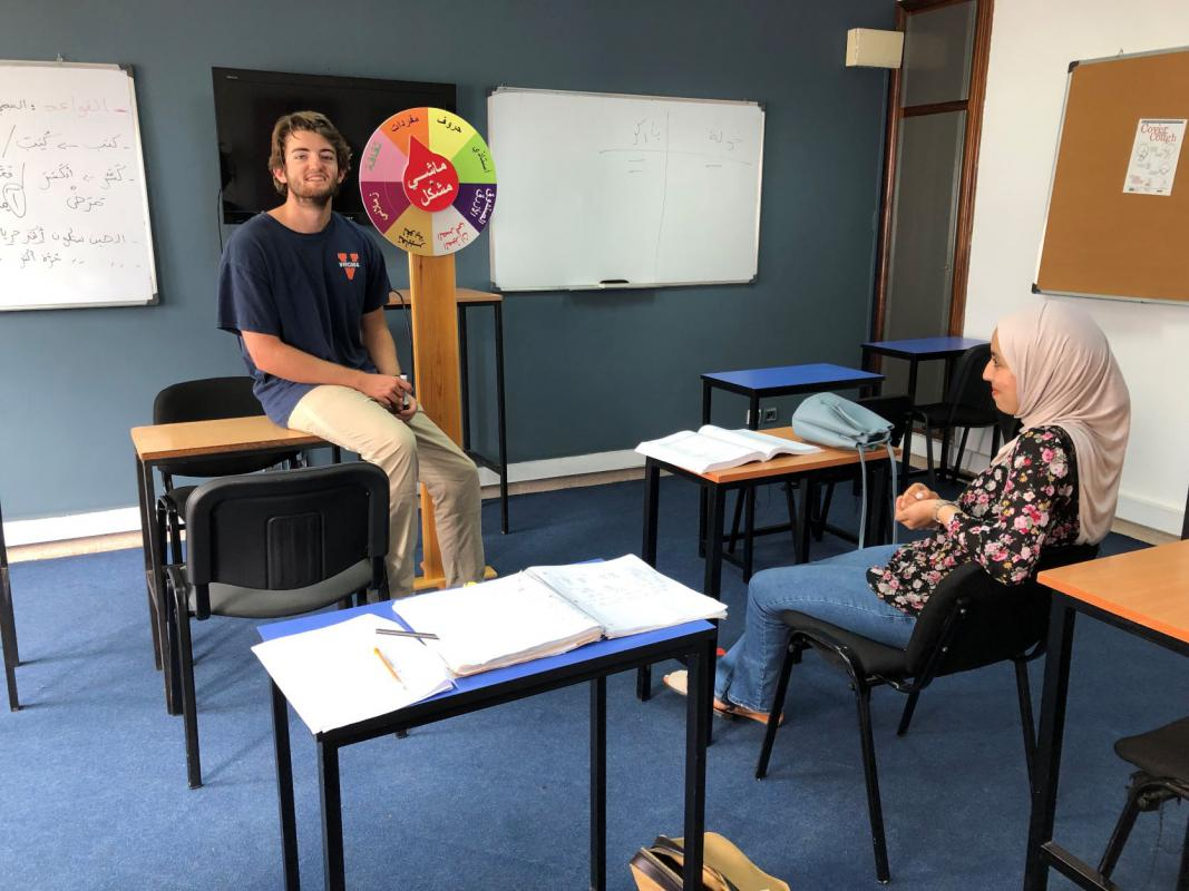 A student sits on a desk in the front of the class presenting to his teacher who is sitting at a student desk in front of him. They are both smiling.