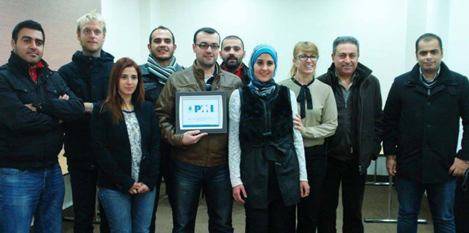 Group of students pose while one holds up a certificate