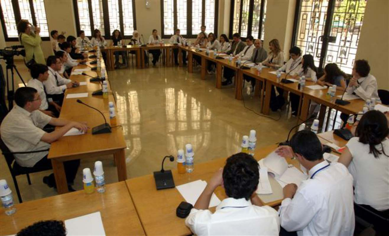 A large group of students sit at multiple long tables facing each other with paper and microphones