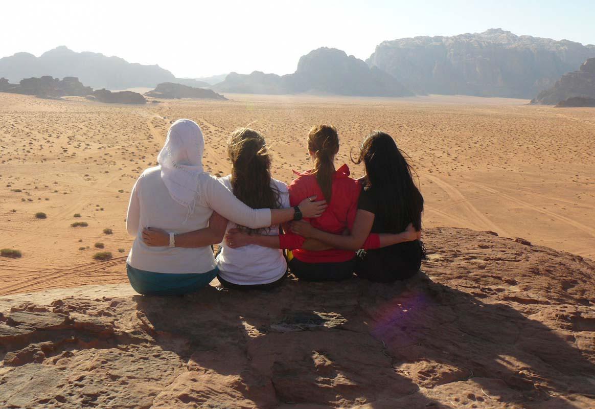 Four women sit on a rock in Wadi Rum, Jordan