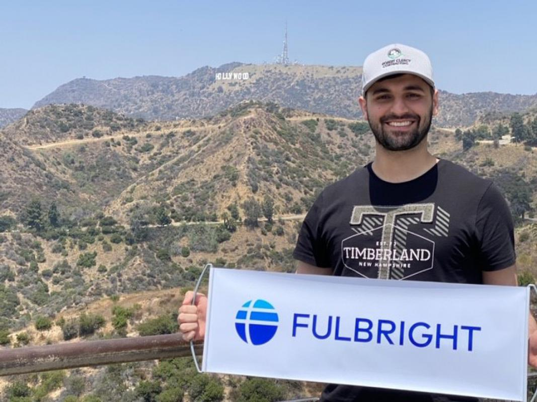 College student in front of Hollywood sign in Los Angeles holding banner with Fulbright program logo