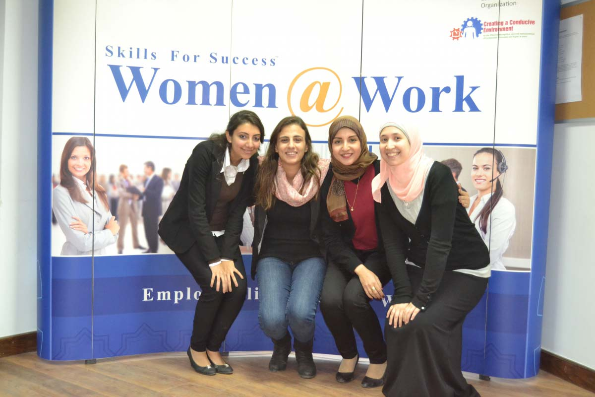 """Female students stand in front of a sign that reads """"Skills for Success: Women at Work"""""""
