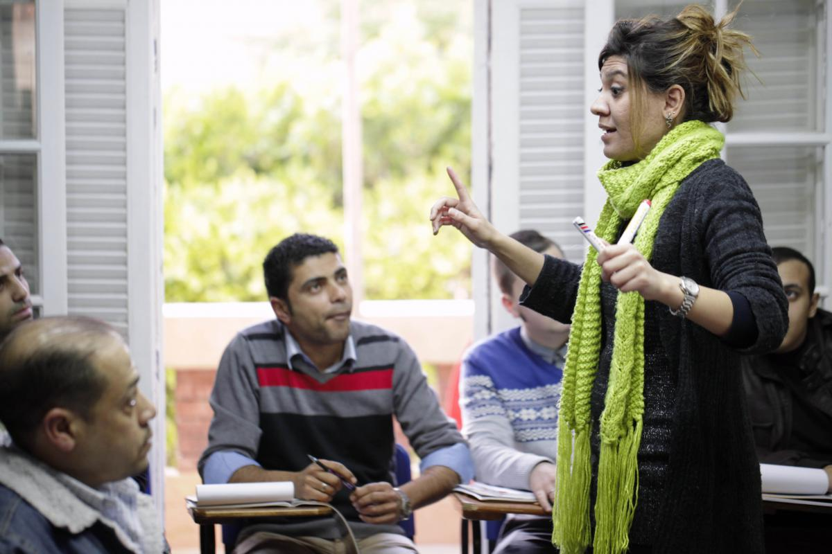 English Teacher talking to students at AMIDEAST field office