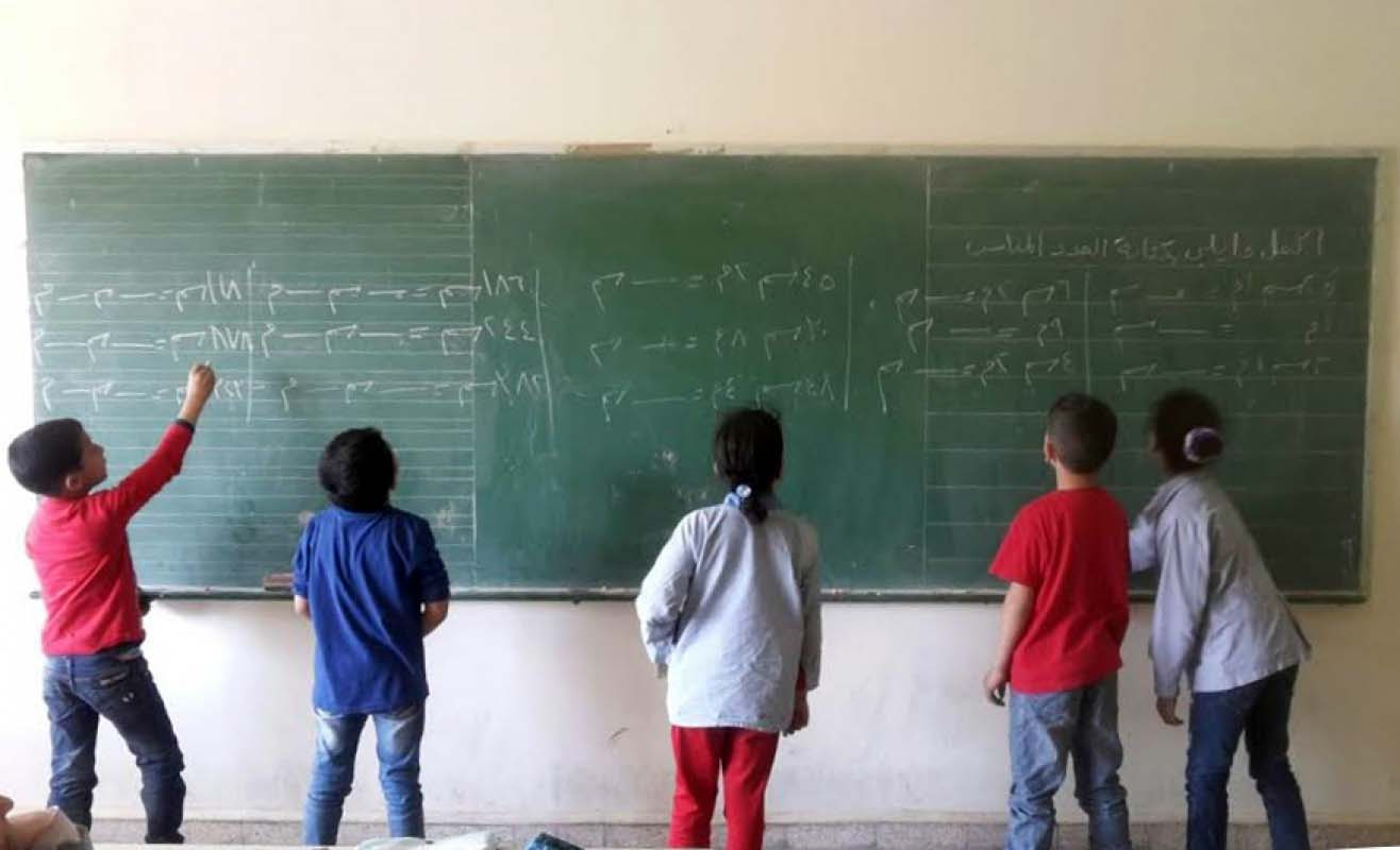 Children writing in Arabic on a blackboard as part of the Ana Iqra project