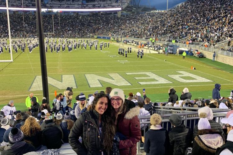 Two students in front of the endzone at a football game