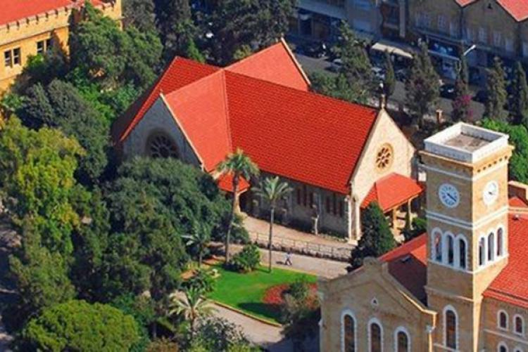 A picture of AUB campus buildings, showing a group of buildings with tiled roofs surrounded by trees