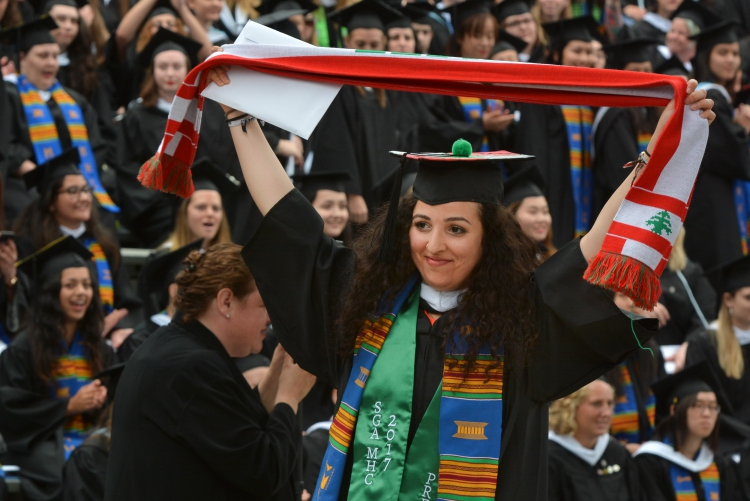 Graduating student holds up a scarf with the Lebanese flag on it at her ceremony