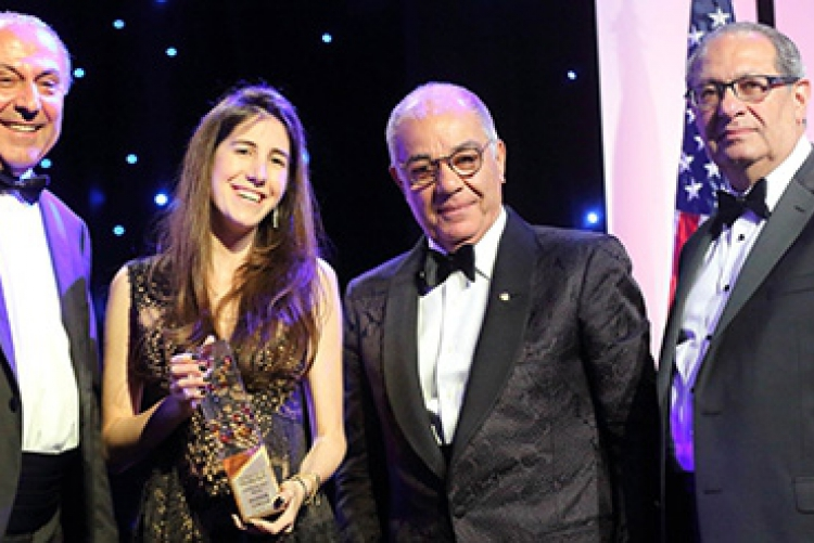 Flanked (left to right) by ALAB Chair Anis Nassar, Gala Chair Harry Nadjarian, and AMIDEAST President and CEO Theodore Kattouf, Nour Semaan holds thEducation Hero Award that she accepted on behalf of her late father, Maroun Semaan.