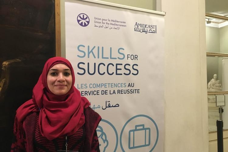 """Women smiles in front of a sign that reads """"Skills for Success"""""""