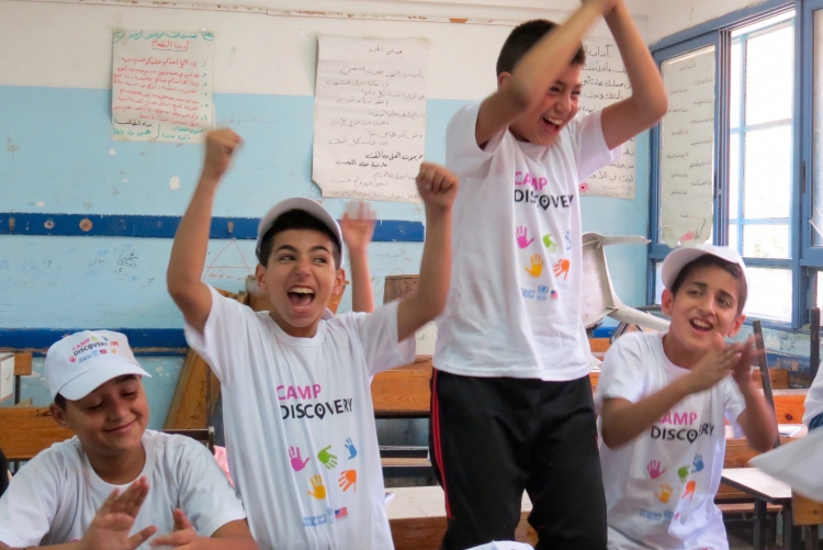 Students wearing Camp Discovery shirts jump and celebrate in a classroom