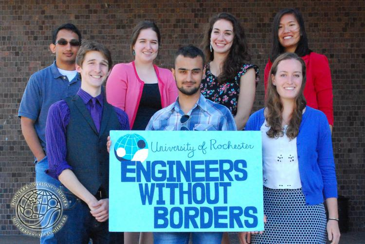 """A group of students at the University of Rochester hold a sign that reads """"Engineers Without Borders"""""""