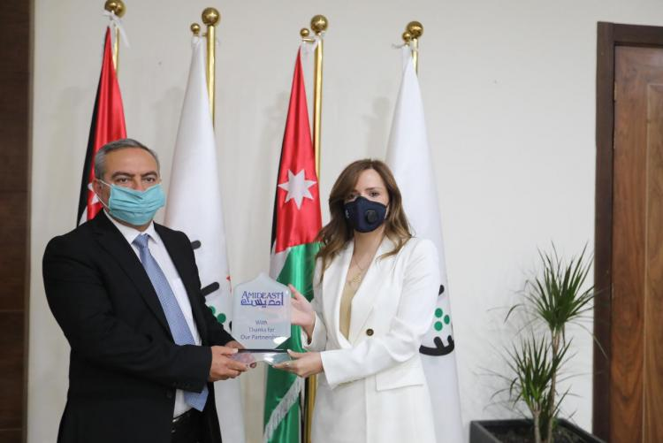 Amideast country director Nour Alrasheed holds plaque with Jordanian Youth Minister