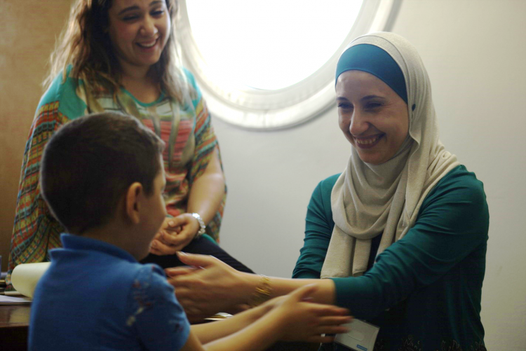 A woman in a medical setting reaches out to a young child