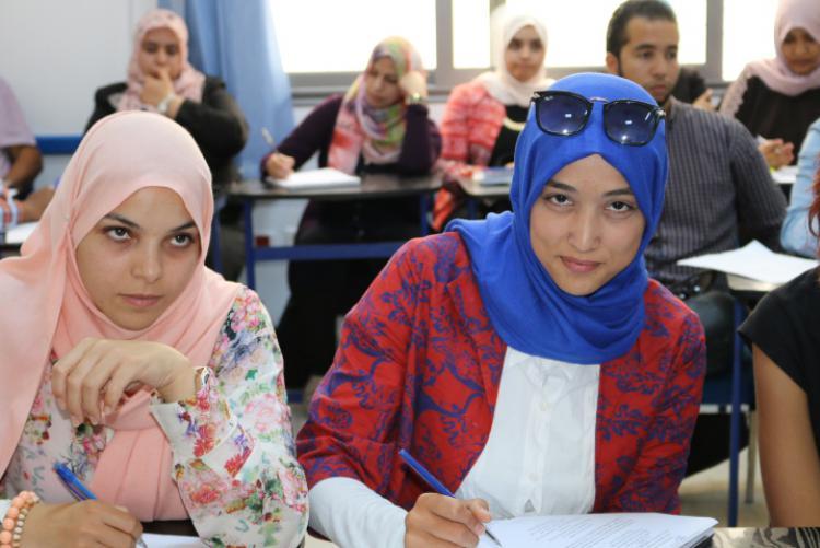 Libyan English teachers write at desks in a classroom during a PCELT training