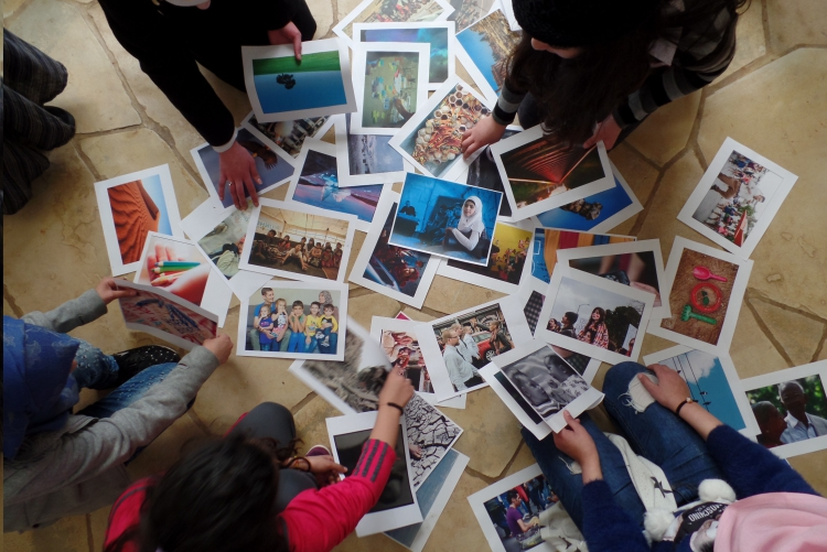 Female students look at a collection of printed photographs