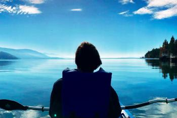 A woman faces away from the camera while sitting in a chair and looking at a lake and mountain landscape in Glacier National Park