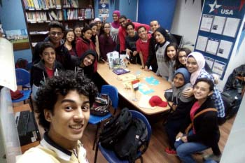 A group of students pose for a selfie while sitting around a table