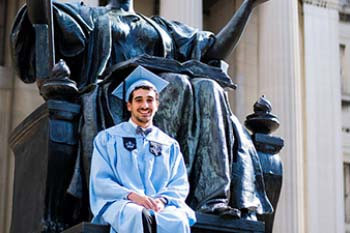 Graduating student poses on statue wearing cap and gown