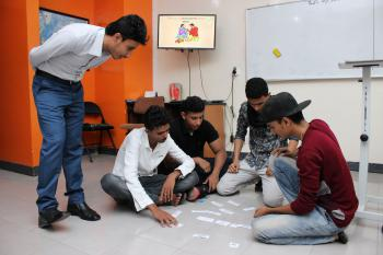 An EFL instructor is supervising a group of students who are sitting on the ground doing a jigsaw activity     y