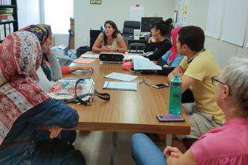 A group of scholars listens to a lecturer during their program.