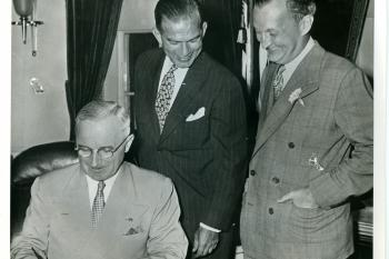 Man  signing Act with two men watching