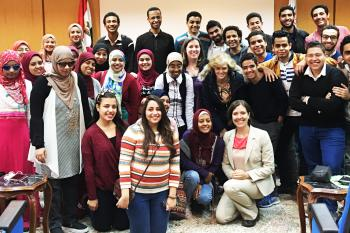 Large group of Egyptian college students group together and smile at the camera