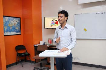 An EFL instructor is standing explaining a lesson in a classroom at AMIDEAST Yemen