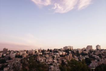 The skyline of Amman at sunset the buildings in the distance and the sky is prominent and a rosy color at the horizon but clear blue at the top.