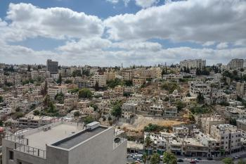 The city of Amman sits under a blue sky with puffy white clouds.