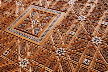 Geometric wood carving with focus in the top left on a square with design inside