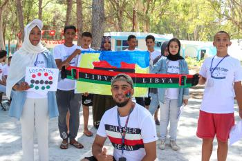 A group of young Libyans at a summer camp, holding the Libyan flag