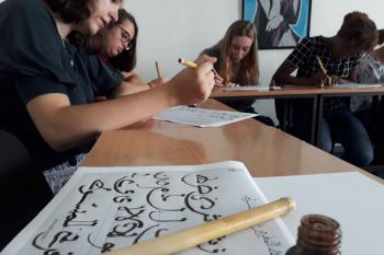 Students work on learning calligraphy. In the foreground is a student's example