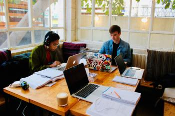 Two students study at a table in a cafe