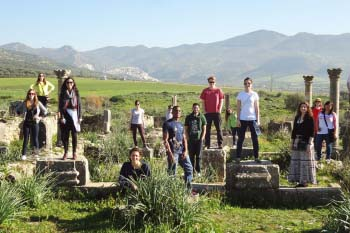 Students stand on columns and the ruins of the Roman city of Volubilis in Morocco