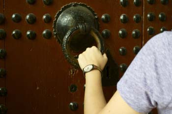 An arm of a student wearing a watch is holding a large door knocker on an old door in Morocco