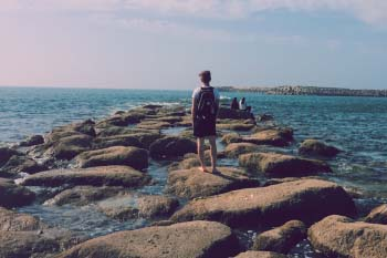 Student walks on rocks jutting into the Atlantic Ocean in Rabat, Morocco